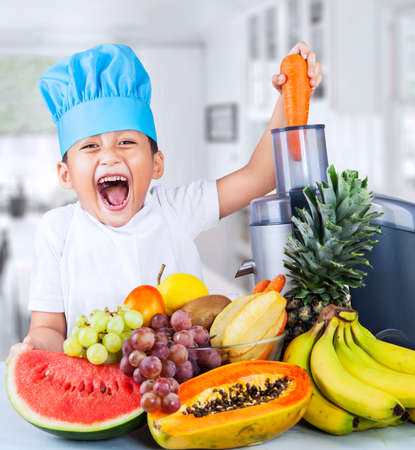 fruit juice: Happy little chef is making healthy fruit juice at home Stock Photo