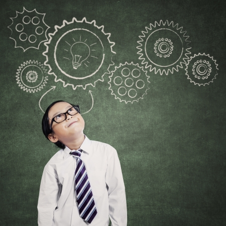 Thinking little businessman with mechanisms on the blackboard photo