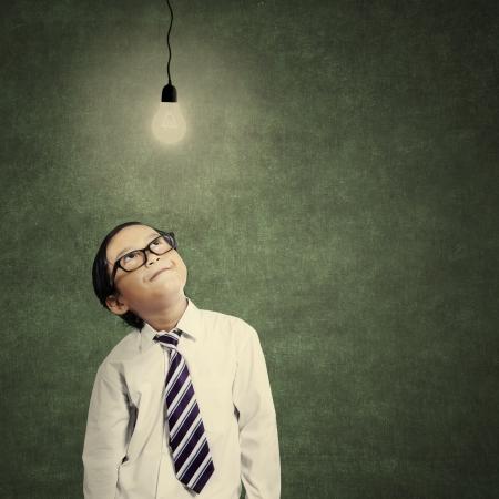 soustředění: Close-up mladého malý podnikatel při pohledu na osvětlené žárovkou ve třídě