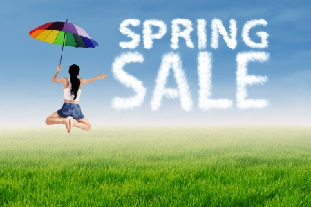 Spring sale clouds and woman jumping over green meadow photo