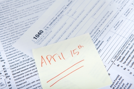 reminder concept: Tax reminder concept with a sticky note of april 15 and a tax form