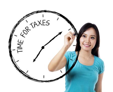 impuestos: Casual mujer dibujando un tiempo para los impuestos sobre pizarra transparente Foto de archivo