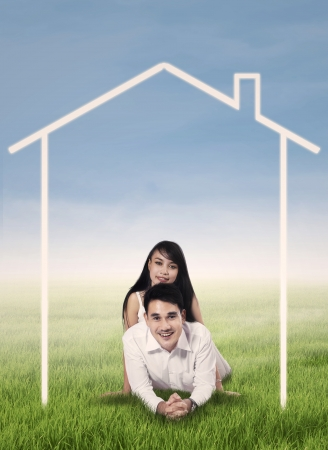 Romantic young couple lying on grass with dream house drawing photo