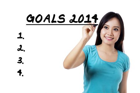 Portrait of casual woman writing the list of goals 2014 photo
