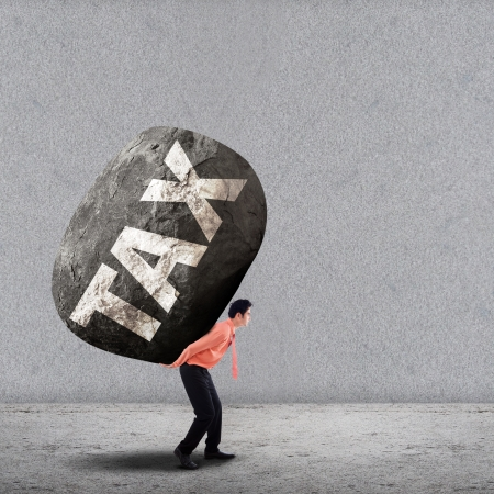 Concept of stress of a businessman carrying a big rock of TAX