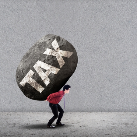 burden: Concept of stress of a businessman carrying a big rock of TAX