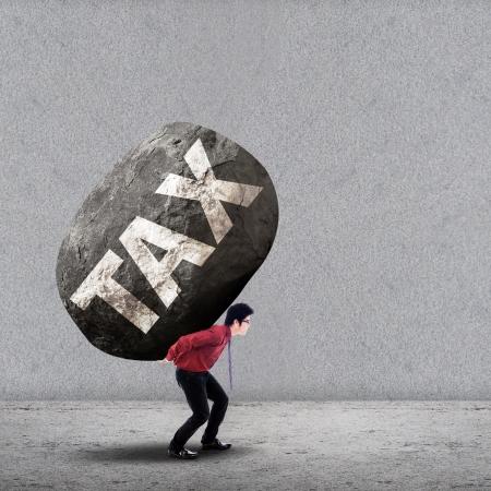 ingresos: Concepto de estrés de un hombre de negocios con una gran roca de IMPUESTO