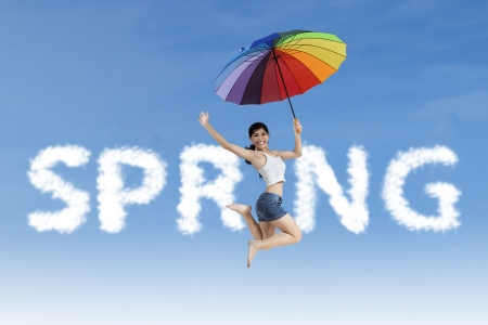 Woman flying with colorful umbrella in the spring word photo