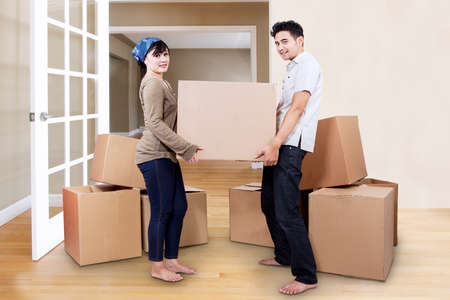 cardboard house: Young couple moving into new home carrying box