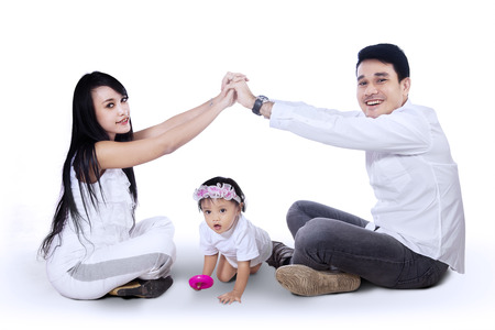 Young happy asian family making the home sign isolated on white background photo