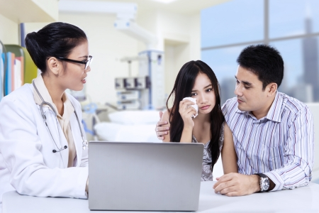 A female doctor explaining bad results to young couple at clinic photo