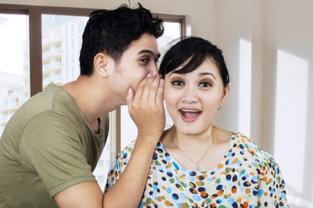 Portrait of a handsome young man whispering a secret to a cute woman  photo