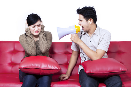Angry boyfriend using speaker at girlfriend sitting on red sofa photo