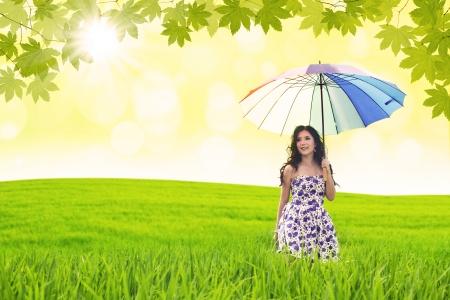 woman umbrella: Beautiful woman holds umbrella in green field Stock Photo