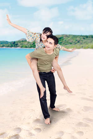 Boyfriend giving piggyback ride at beach photo