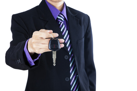 Successful businessman offering a car key isolated on white background photo