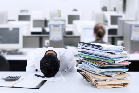 Tired young businessman is sleeping at desk in office