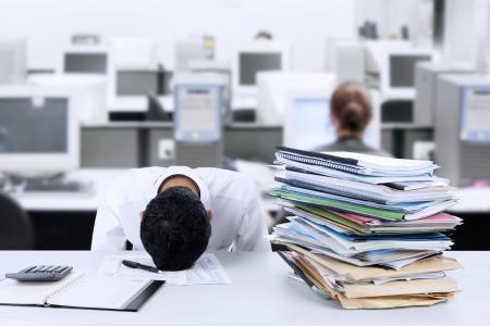 Vermoeide jonge zakenman slapen op het bureau in het kantoor Stockfoto
