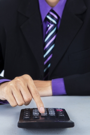 Close up of businessman using a calculator photo