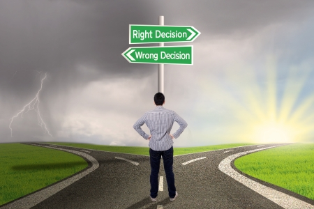 right vs wrong: Businessman is standing on the road with a sign of right vs wrong decision Stock Photo