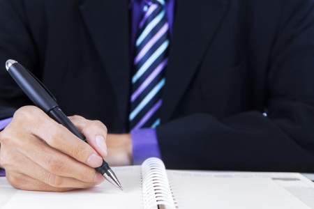 Close up of businessman writing on a book at office photo