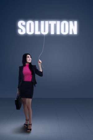 Beautiful young businesswoman holding a solution photo