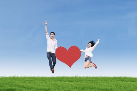 Asian couple jumping with heart card photo