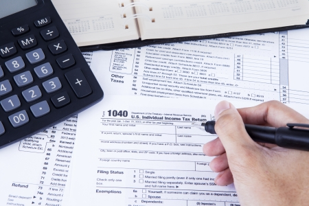 Hands of businessman filling tax form photo