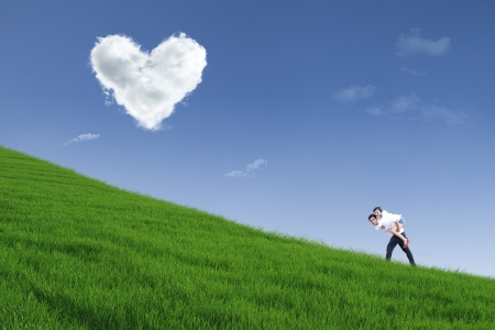 under heart: Guy giving piggyback ride on hill under heart cloud Stock Photo