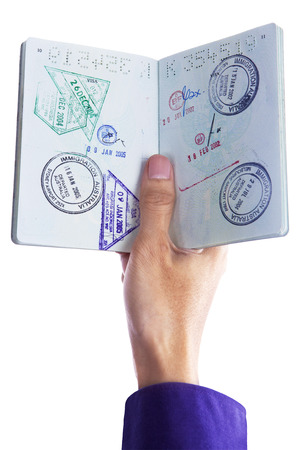 Close up of hand holding a passport isolated on white background