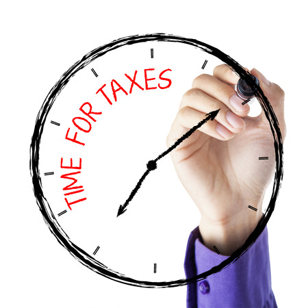 Hands writing time for taxes with marker on face clock photo