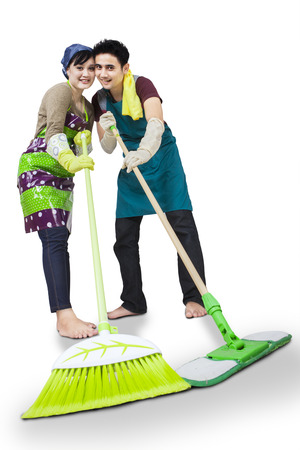 Portrait of young couple cleaning the floor with mop and broom isolated on white Stock Photo