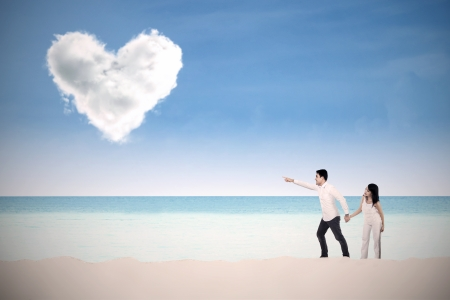 Happy couple walking and pointing at clouds shaped of heart on a deserted beach photo