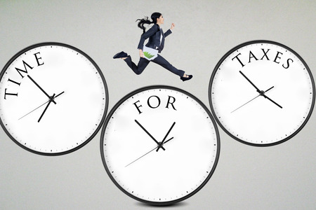 Businesswoman running over the clocks with time for taxes photo