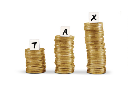 Word tax on gold coin stacks isolated on white background photo