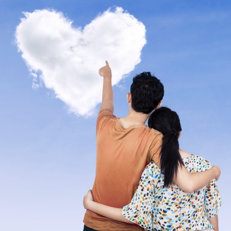 Young couple pointing at clouds shaped of heart on the sky photo