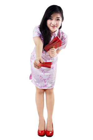 Smiling young girl giving red envelopes. Isolated on white background photo