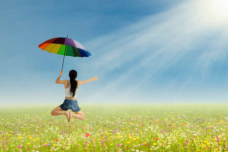 Young girl jumping with umbrella on the park photo