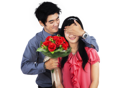 A man giving flowers to his wife - isolated on white background Stock Photo