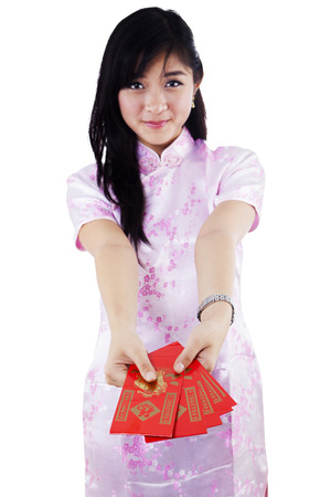 qipao: Smiling asian woman giving red envelopes. Isolated on white background