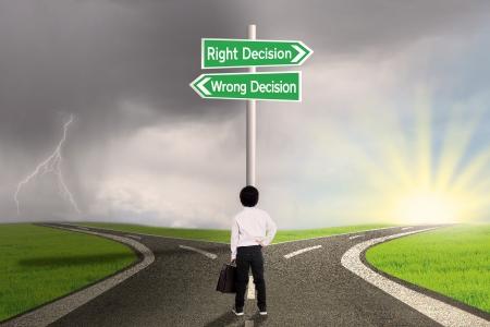 Pequeño niño de negocios está de pie en el camino con un signo de derecha vs decisión equivocada Foto de archivo