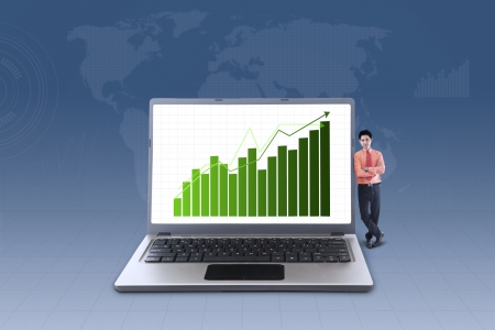 Businessman standing next to laptop with increase bar chart on blue background photo