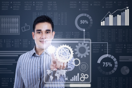 controling: Businessman working with gear in a futuristic interface