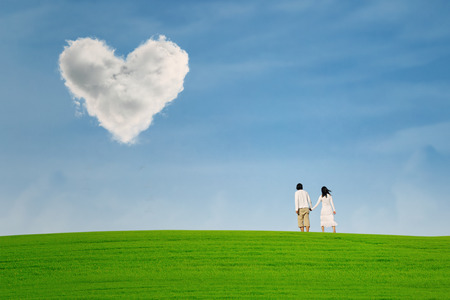 heart under: Couple at green field under heart shape cloud over the hill