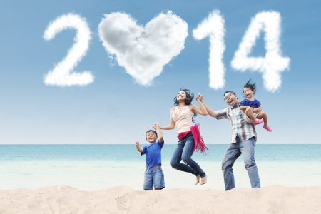 Happy family having fun in the beach with heart shaped cloud of new year 2014 photo