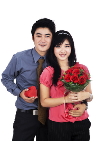 Attractive young couple with a gift and flowers - isolated on the white background photo