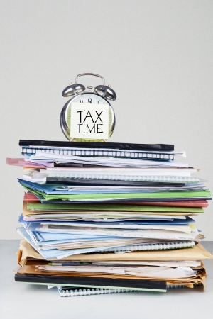 Tax time on an alarm clock face over the stack of documents photo