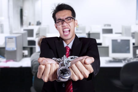 Stress businessman with hands chained at office photo