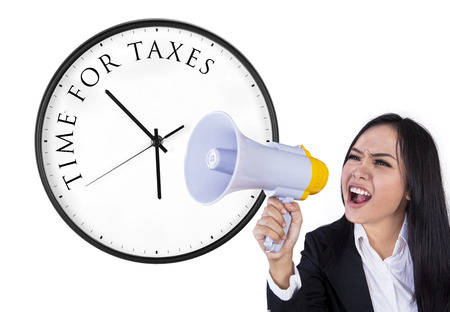 Business woman announcing time for taxes with megaphone photo