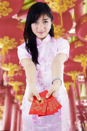 Asian woman with chinese traditional dress holding red packet gift photo